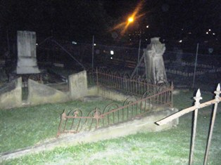 Apparition leaning on large headstone